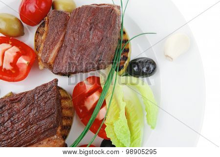 grilled meat : beef ( lamb ) garnished with tomatoes , green and black olives on white plate isolated over white background