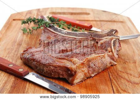 meat food : roast rib on wooden plate with thyme isolated over white background . shallow dof