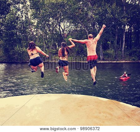 three people jumping off a concrete structure into a river toned with a retro vintage instagram filter effect app or action