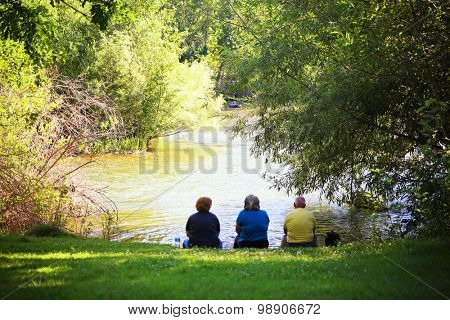 senior people sitting in summer near a lake or river during sunset