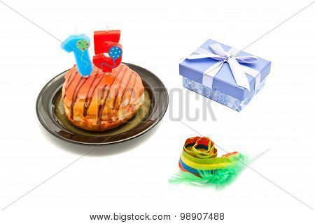 Donut With Fifteen Years Birthday Candle, Whistle And Gift On White