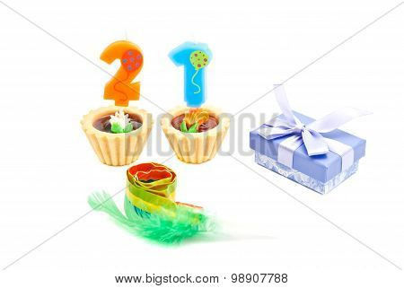 Cakes With Twenty One Years Birthday Candles, Whistle And Gift On White