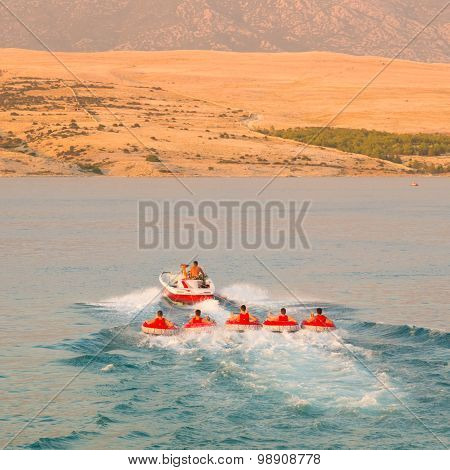 Kids tube riding tawed by speedboat.