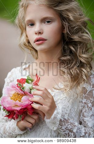 lifestyle portrait little bridesmaid  with bouquet.  Beautiful Teenage Girl Having Fun inthe spring  Park . cute little bridesmaid with bunch of flowers wedding concept  cute princess girl Happy little schoolgirl with flowers.Close up