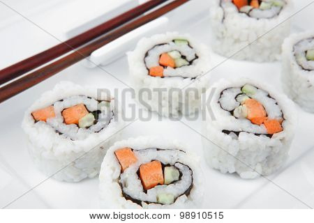 Maki Sushi - California Sushi Roll with Avocado, Cream Cheese and Raw Salmon inside. With wasabi . isolated over white background on square plate