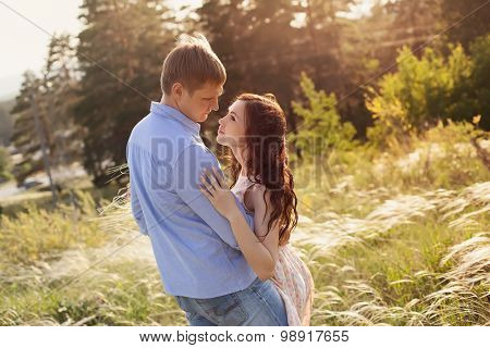 lovers walking in a field at sunset