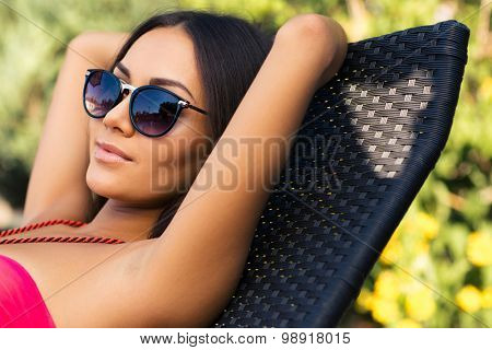 Portrait of a pretty woman sunbathing on the deckchair outdoors