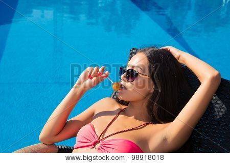 Portrait of a pretty girl lying on deckchair with lollipop outdoors