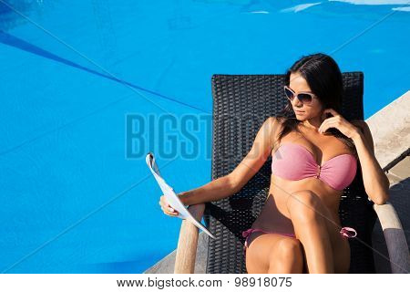 Portrait of attractive young woman reading magazine on deckchair near swim pool outdoors