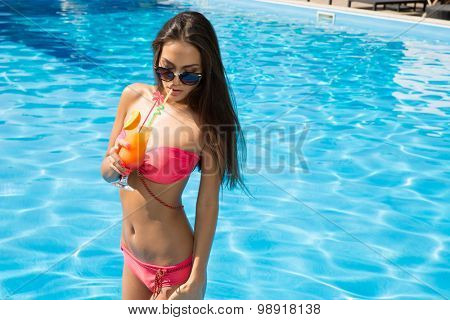 Portrait of a cute woman in sunglasses drinking cocktail in swimming pool