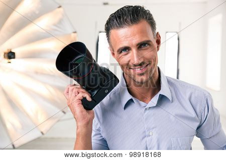 Portrait of a handsome photographer holding camera and looking at camera in studio