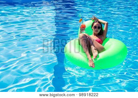 Portrait of a young woman lying on air matress with cocktail in swimming pool outdoors
