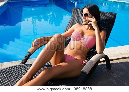 Happy beautiful woman talking on the phone on deckchair outdoors