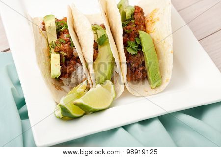 three homemade soft tacos with ground meat, avocados, cilantro and rice