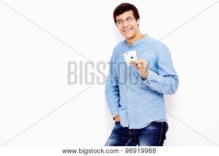 Young hispanic man wearing jeans and glasses smiling and holding two aces (hearts and clubs) in his hand against white wall - gambling concept