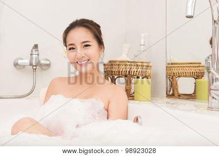 Portrait of beautiful woman relaxing in a spa bath with foam