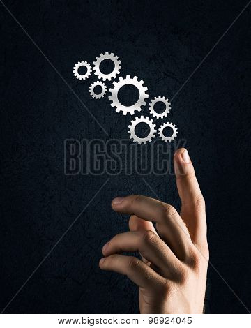 Close up of hand and gears mechanism on black background