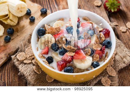 Pouring Milk In A Bowl With Cornflakes And Fruits
