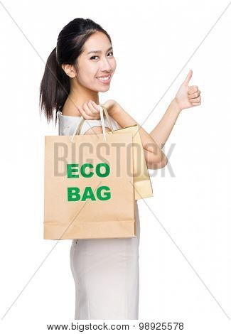 Woman with thumb up gesture and holding shopping bag for showing eco bag