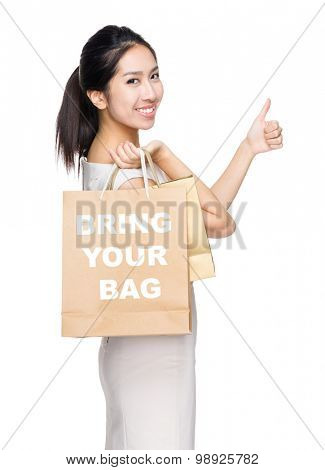Woman with thumb up gesture and holding shopping bag for showing showing bring your bag