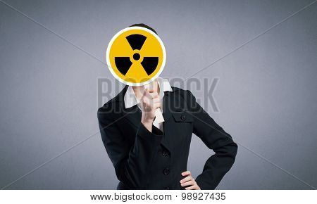 Unrecognizable businesswoman hiding her face behind radioactivity sign