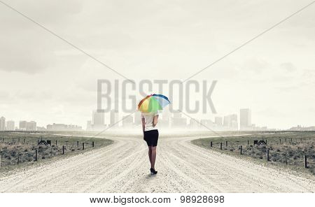 Young pretty businesswoman with rainbow colorful umbrella walking on road
