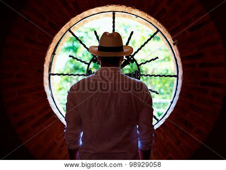 Young Adult Man Standing In Front Of Round Window In Dark Room