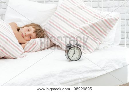 indoor portrait of young happy smiing child girl sleeping in her bed, happy morning time
