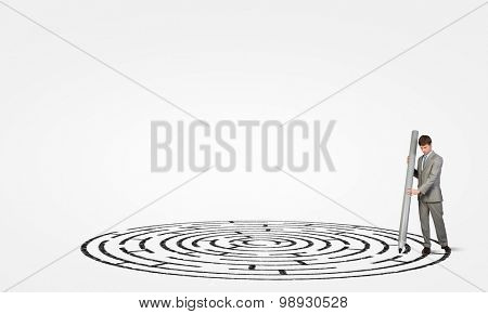 Young businessman drawing maze on floor with huge pencil
