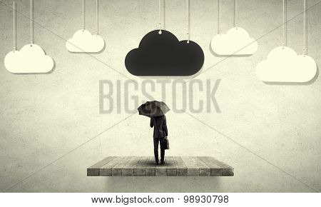 Back view of businessman with black umbrella and black cloud above