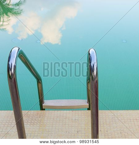 Steel Stair Of Green Swimming Pool With Sky Reflection