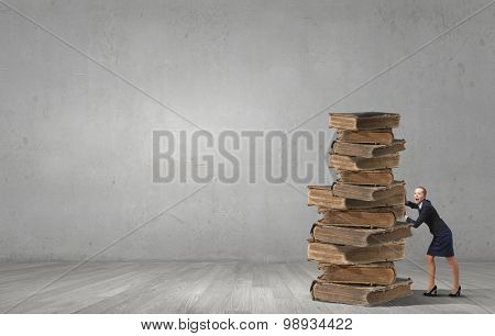Young woman pushing huge pile of old books