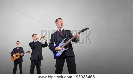 Young man in suit and people playing different music instruments