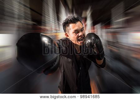 Young aggressive businessman training shadow boxing at gym