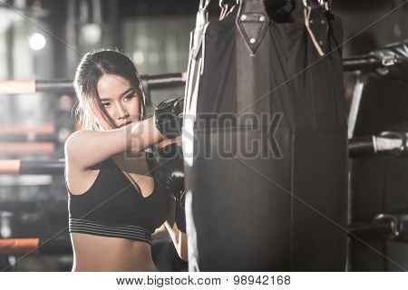 Beautiful Female Punching A Bag With Boxing Gloves at the gym