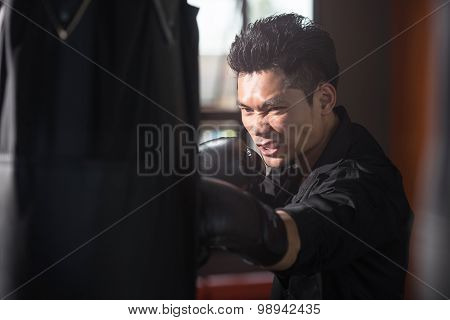 Young Businessman Fighter Training On A Punching Bag In The Gym.