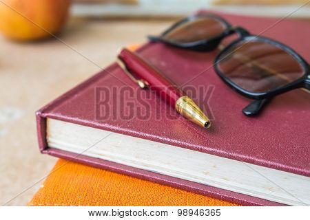 Pen And Glasses On Books.