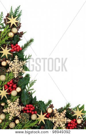 Christmas abstract background border with gold star and snowflake bauble decorations, holly, ivy and fir over white.