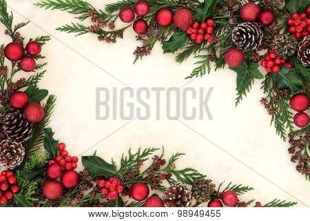 Christmas abstract background border with red bauble decorations, holly and winter greenery over old parchment paper.
