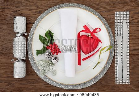 Christmas holiday dinner place setting with plate, napkin, cutlery, sparkling silver and red bauble decorations with holly, mistletoe over oak table background.