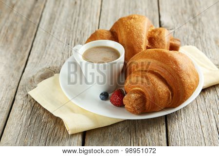 Fresh Tasty Croissants With Berries And Coffee On Grey Wooden Background