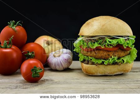 Ciabatta And Falafel Burger With Vegetables On Wood