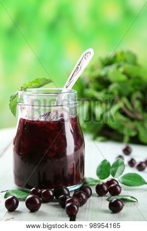 Jar of gooseberry jam on wooden table on natural background