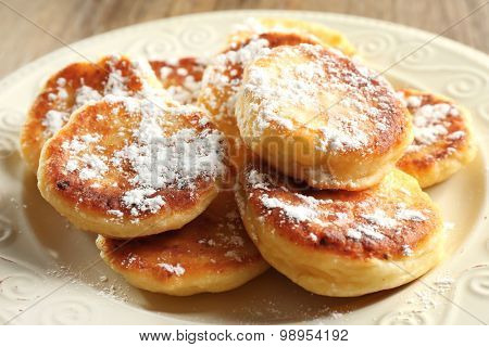 Fritters of cottage cheese in plate on wooden table, closeup