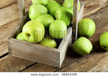 Ripe green apple in crate on wooden table close up