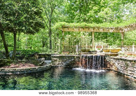 Fountain And Stone Wall At A Garden Lake