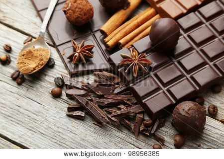 Dark Chocolate Bar With Coffee Beans And Cinnamon On Grey Wooden Background