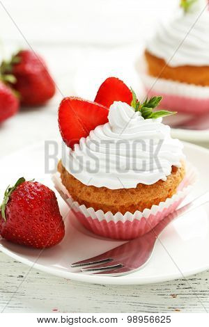 Tasty Cupcake With Strawberry On White Wooden Background