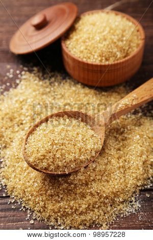 Brown Sugar In Spoon On Brown Wooden Background