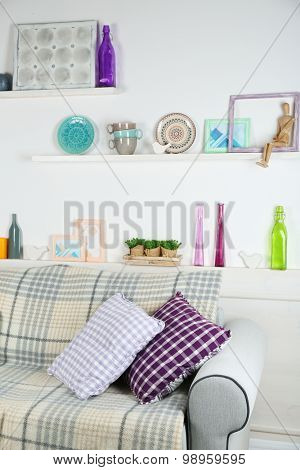 Wooden shelves with decorative things above sofa in room